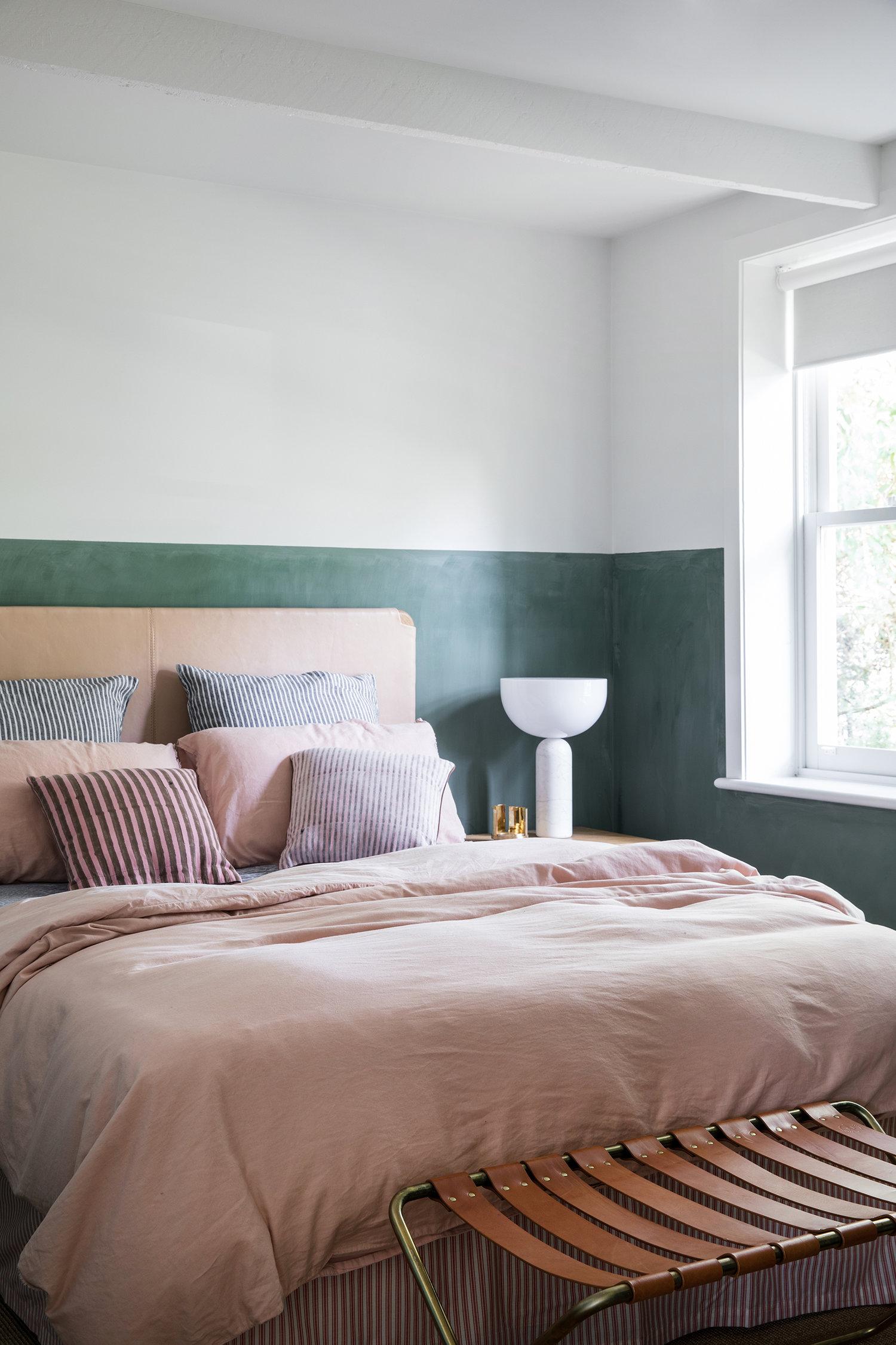 demi-mur peint en vert dans la chambre principale avec tête de lit en cuir et draps en lin | Coco Kelley