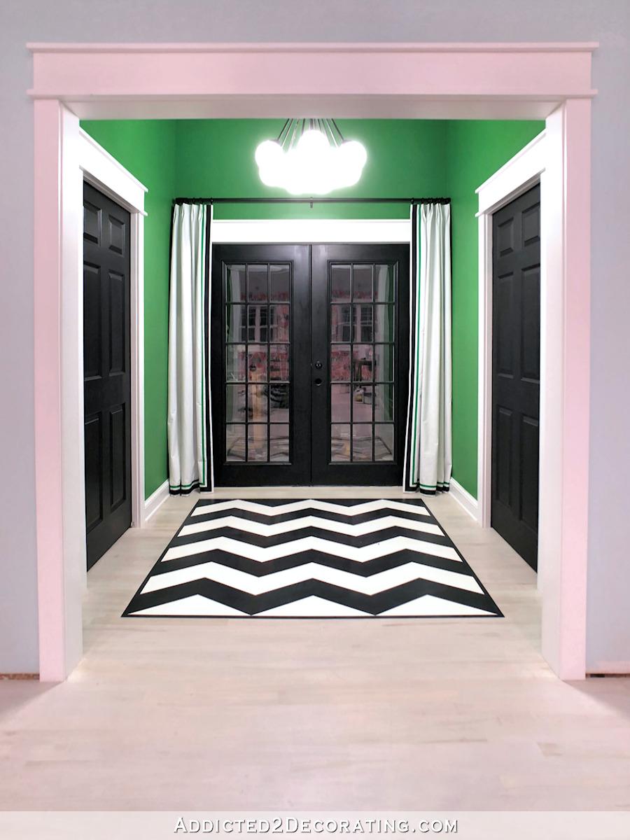 entrée arrière du studio avec un plancher en chevron peint et des portes peintes en noir