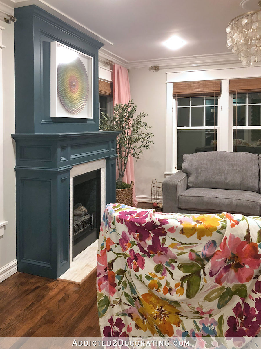 Nouveau canapé en chenille grise avec drapé rose et tissu à motif floral - vue de la cuisine