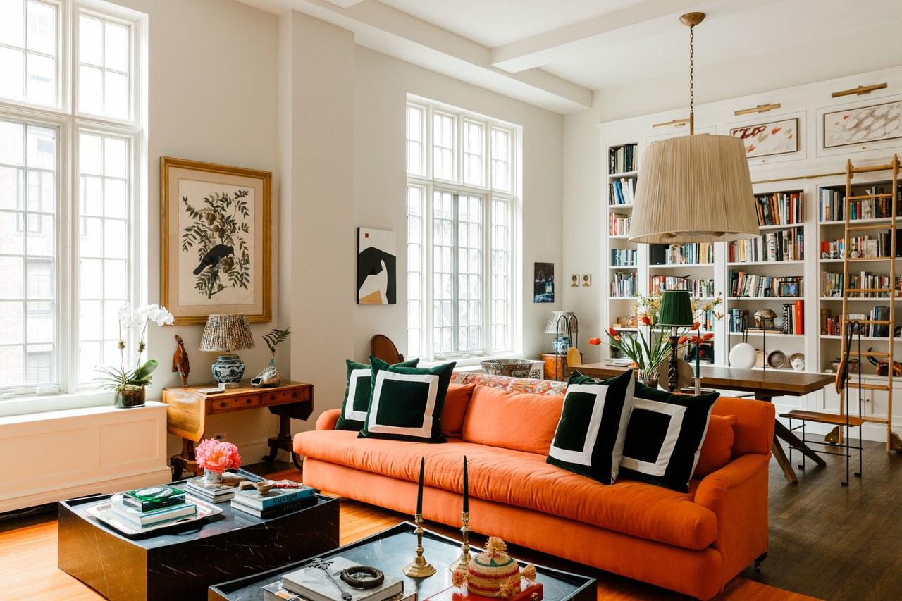 canapé orange dans un espace salon loft blanc | la maison de james hirschfeld via arch digérer