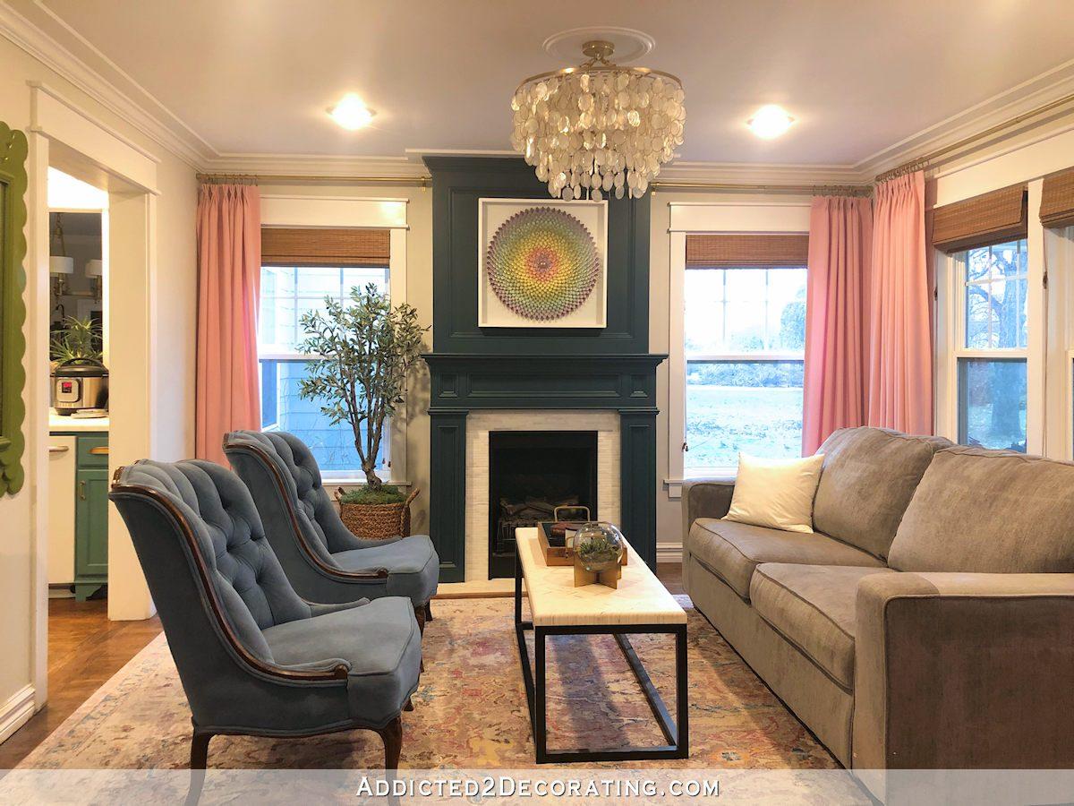 salon actuel avec cheminée turquoise, rideaux roses, canapé gris, tapis gris et lavande