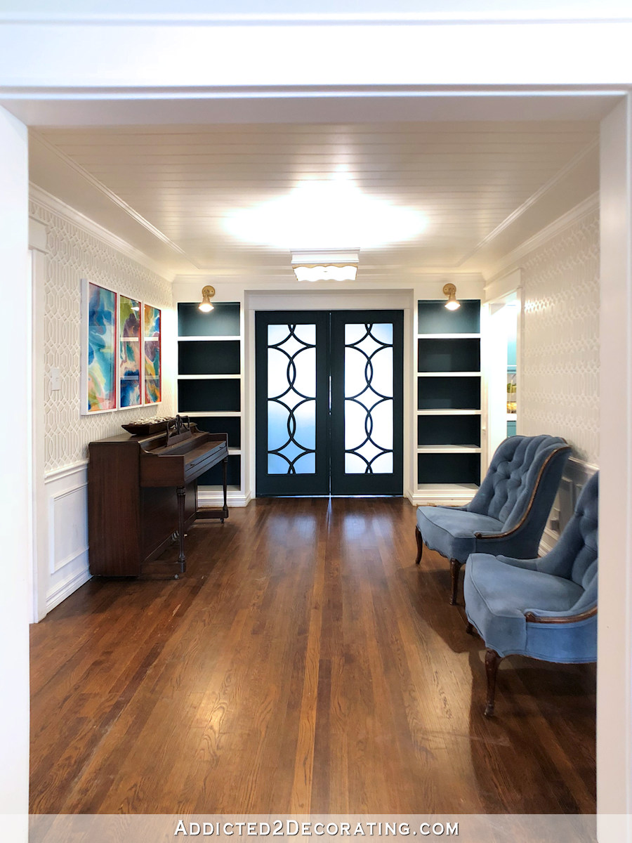 salle de musique actuelle avec le dos des bibliothèques peint sarcelle foncé, portes sarcelle foncé et murs blancs et gris