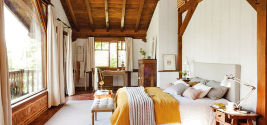 large open bedroom with exposed wood beams and rustic refined style with warm accents